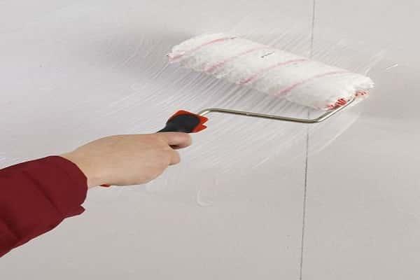 нанесение клея на поверхность перед тем как клеить стеклохолст на гипсокартон