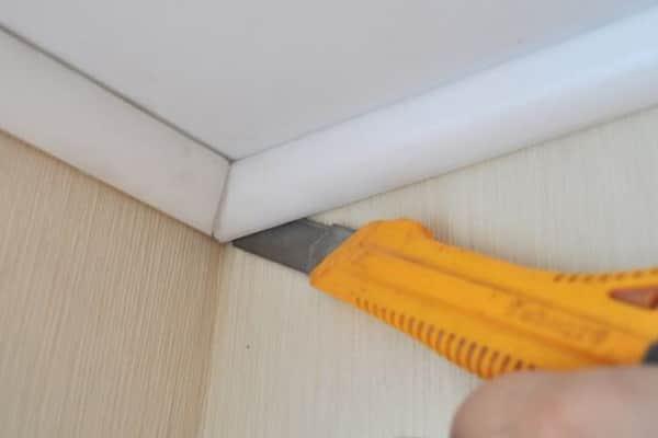 как снять плинтус с натяжного потолка при помощи канцелярского или строительного ножа